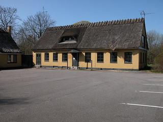 Hjortøgaard før branden i 2011 og Bygning 77, som huser Naturstøttepunkt Hjortøgaard, for enden af Sandet, ca. 150 m fra den nedbrændte gård.